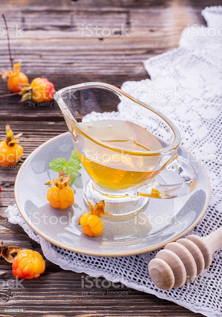 Cloudberry honey in a gravy boat on  saucer with ripe stock photo