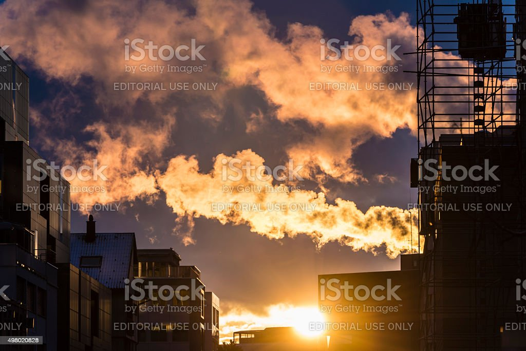 Clouds and factory smoke over industrial area at sunrise stock photo