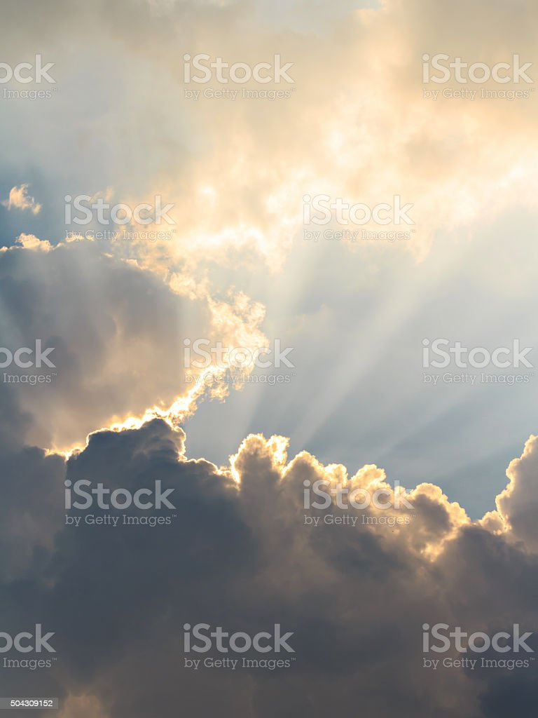 Clouds and sun beams on evening time stock photo