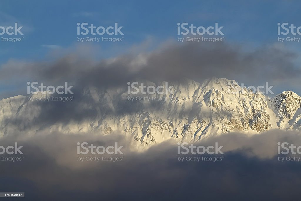 Clouds and sun juxtaposed upon mountain. royalty-free stock photo