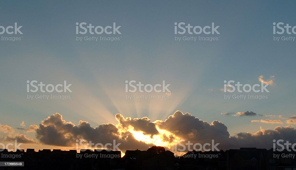 Clouds and Sun Over Houses stock photo