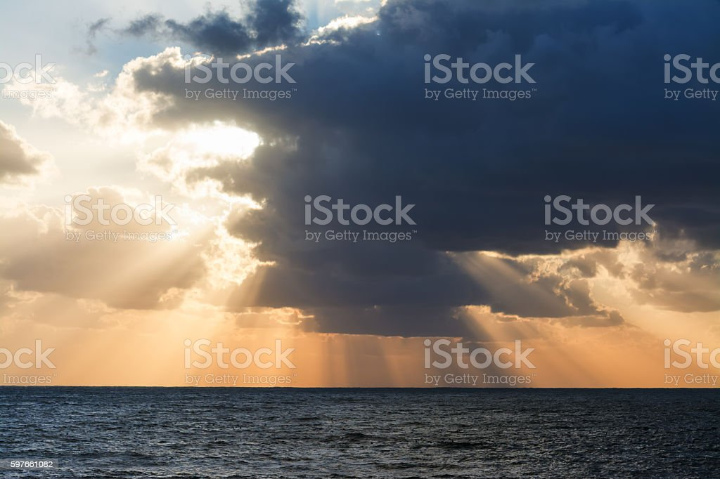 clouds and sun rays at sunset stock photo