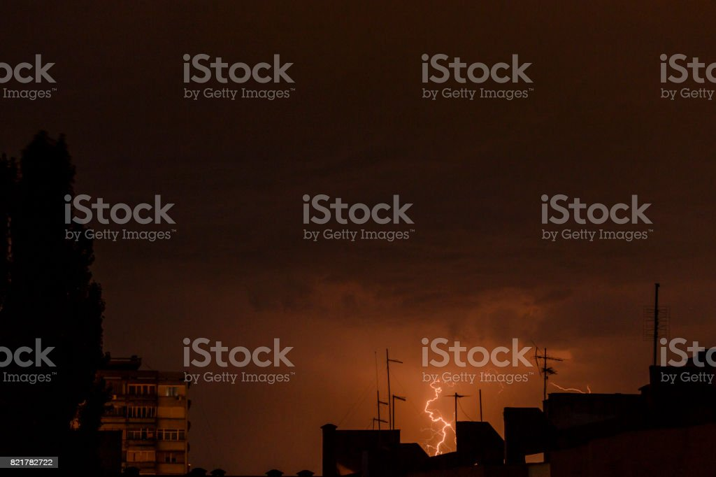 Clouds and thunder lightnings and storm over city. stock photo