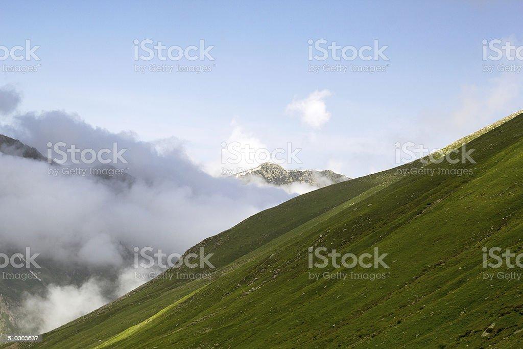 Clouds below mountain stock photo