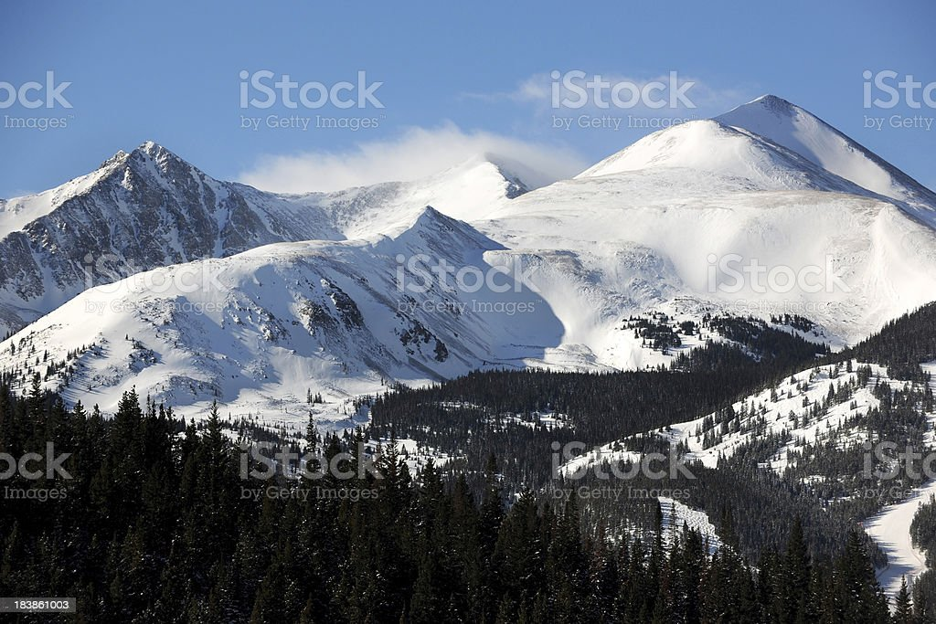 Clouds Blowing Across Snowy Mountain Range stock photo