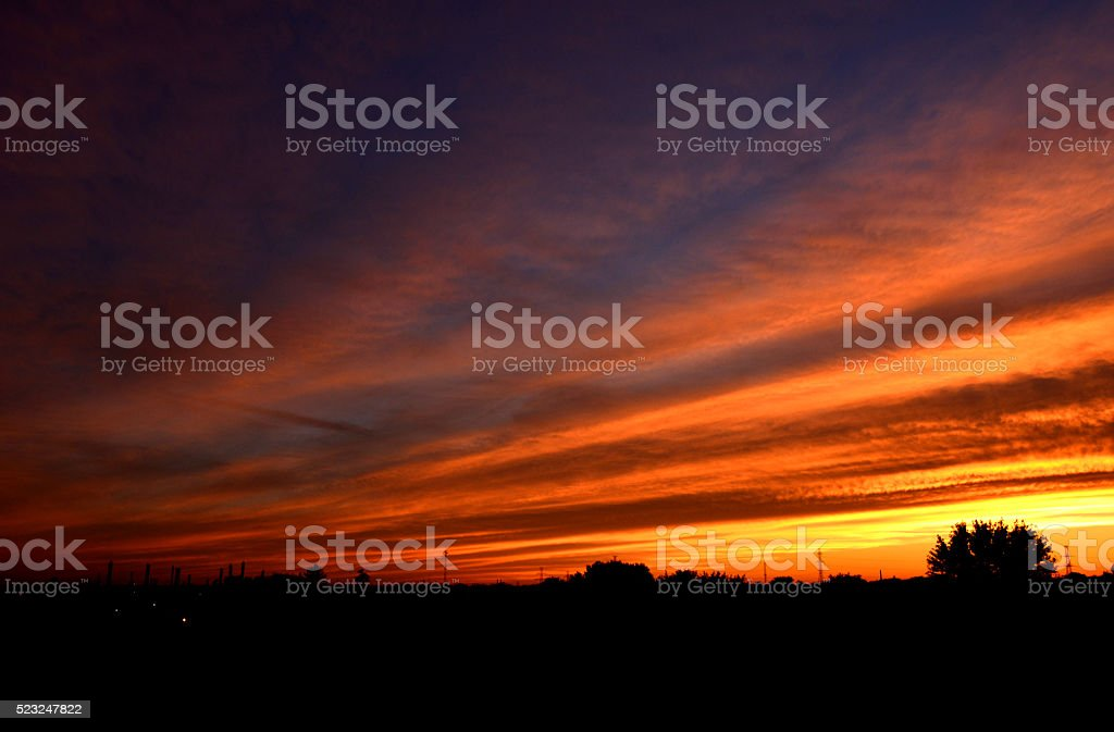 Clouds curve with this sunset with purple, orange, yellow stock photo