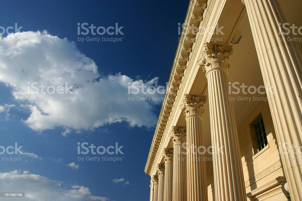 Clouds drifting above golden columns across a blue sky royalty-free stock photo