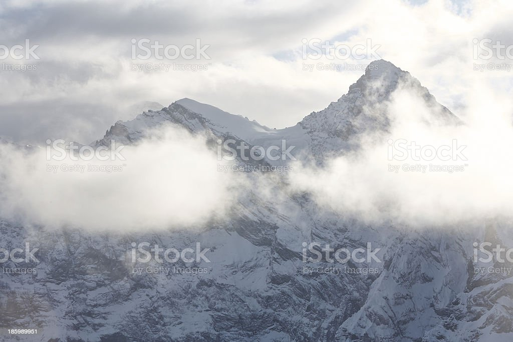clouds hover over the mountain peaks royalty-free stock photo