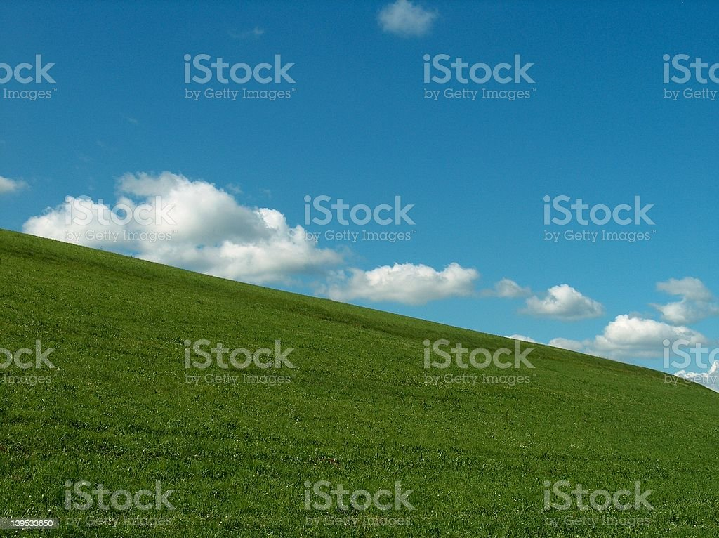 Clouds over green grass - II stock photo
