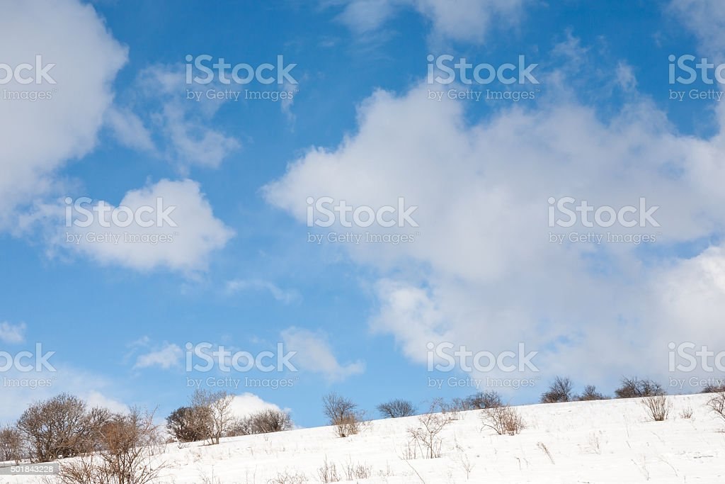 Clouds over winter snowy landscape stock photo