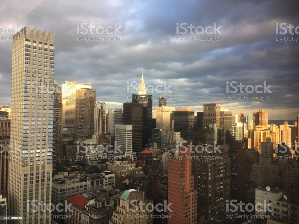 Clouds part and sun shines down on Midtown Manhattan, skyscrapers glowing in the sunlight.  Storm clouds over New York City skyline, taken from tall skyscraper office window. Looking out window. stock photo
