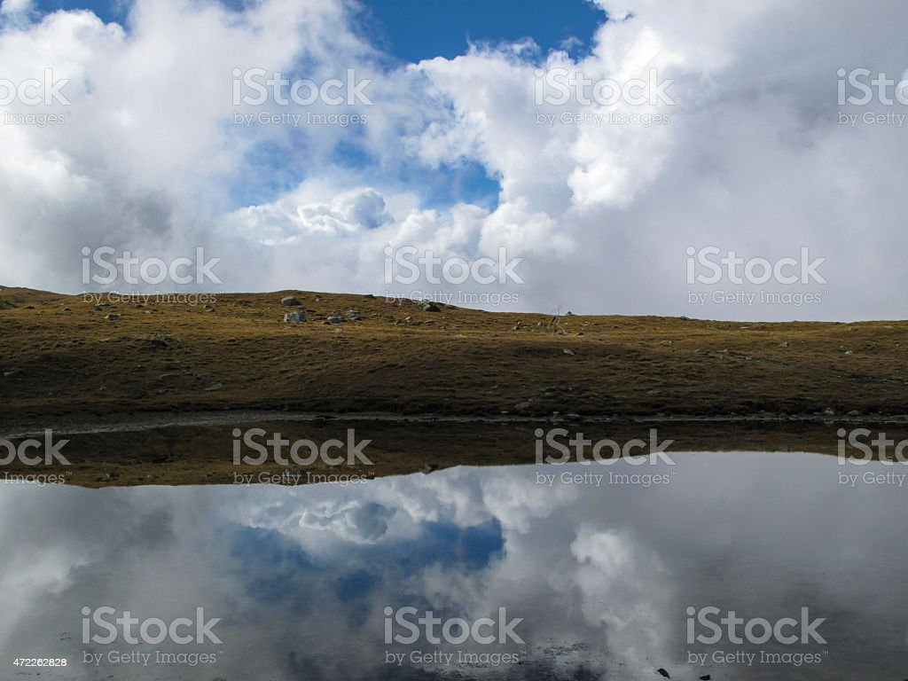 Clouds reflected in alpine lake stock photo