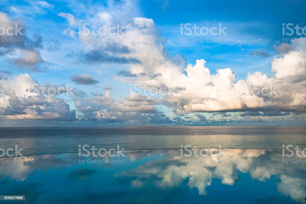 Clouds reflected in an infinity pool near the sea stock photo