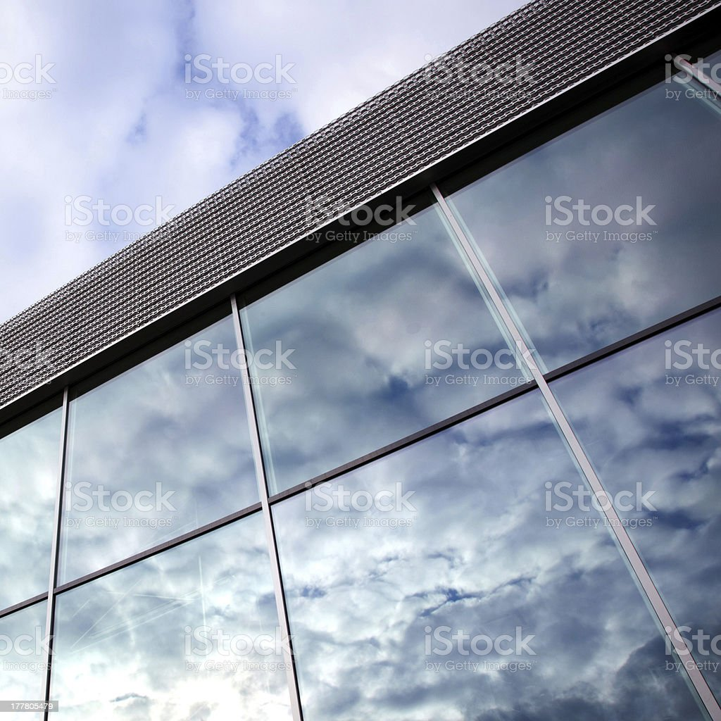 clouds reflected in windows of office building royalty-free stock photo
