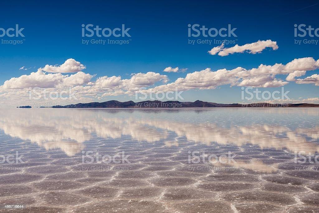 clouds reflecting in the uyuni salt lake in bolivia stock photo