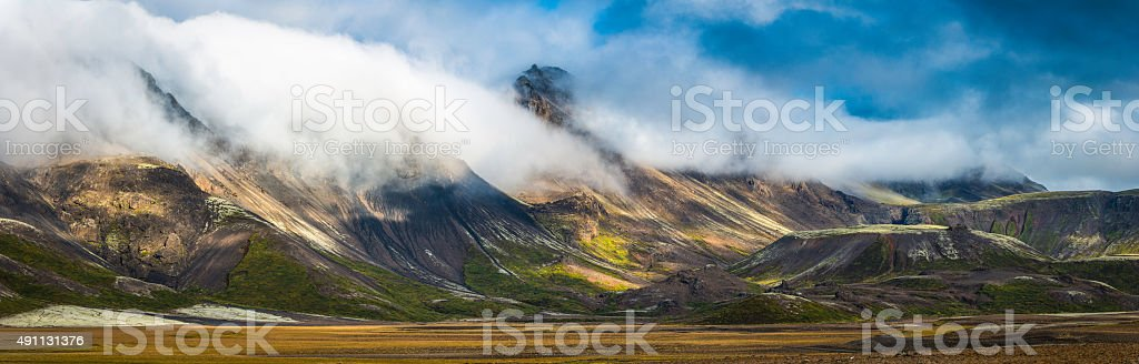 Clouds rolling over dramatic mountain panorama to valley below Iceland stock photo