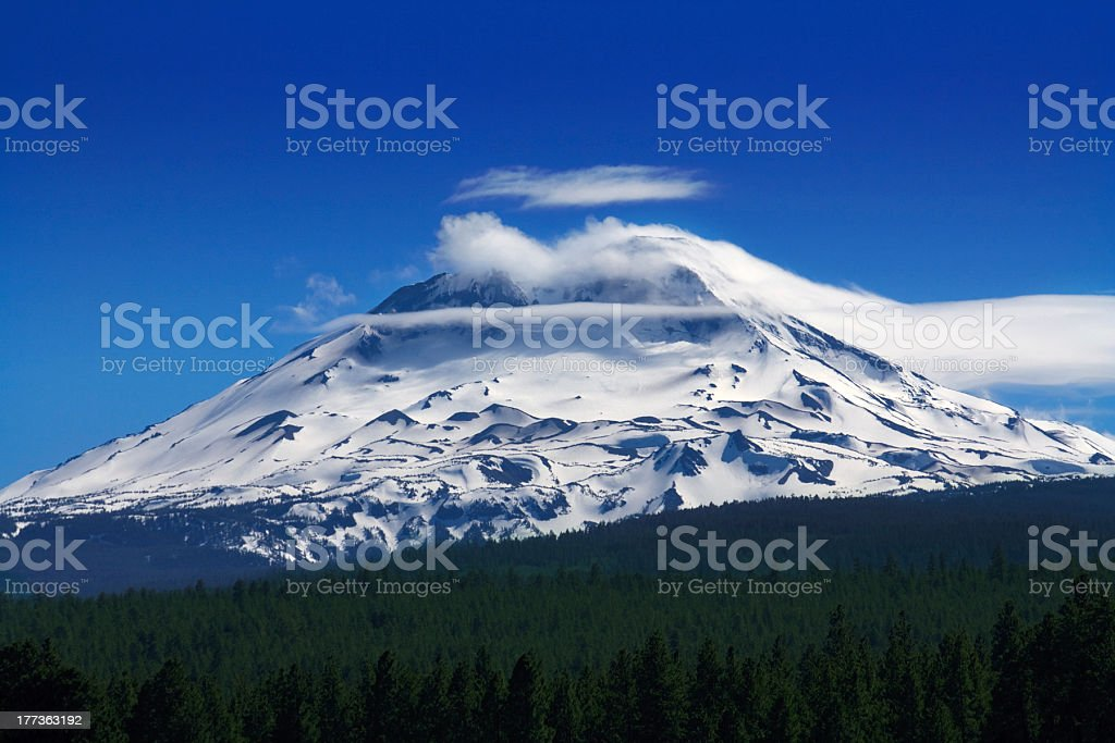 Clouds streaming off a mountain stock photo