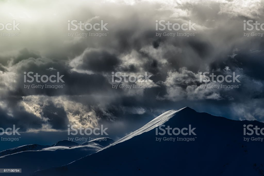 Clouds with spectacular colors in a mountain landscape stock photo