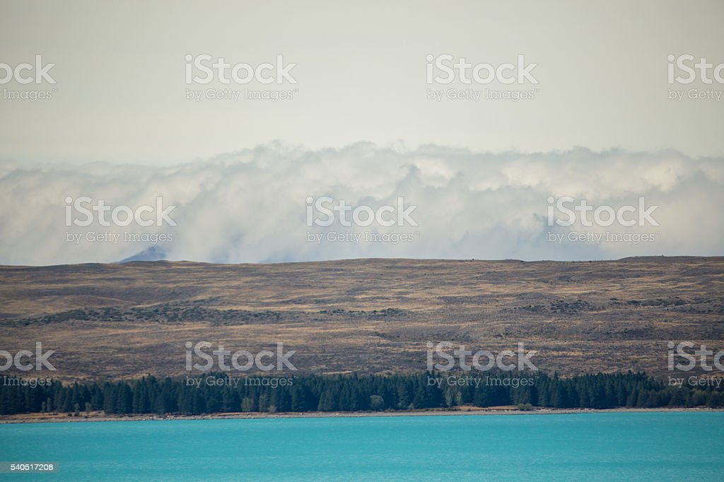 Clouds wrapping over mountain range stock photo