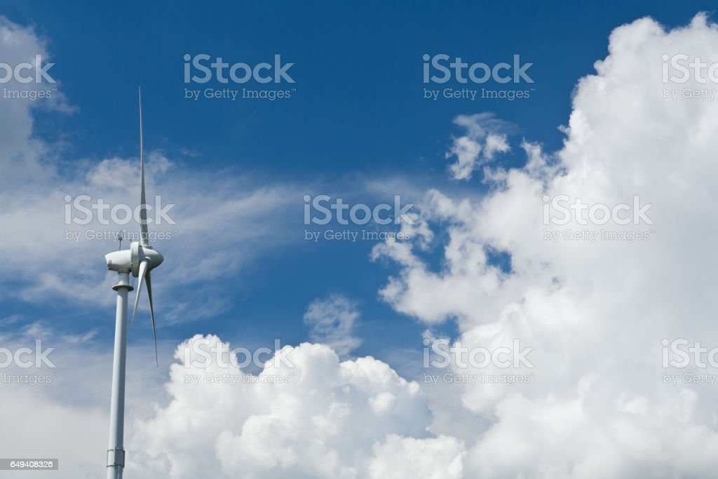 Cloudscape of a green wind turbine stock photo
