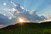 Cloudscape with sun rays over small green hills