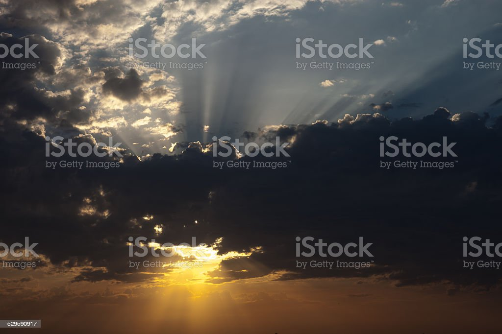 Cloudscape with the sun rays radiating from behind the cloud stock photo