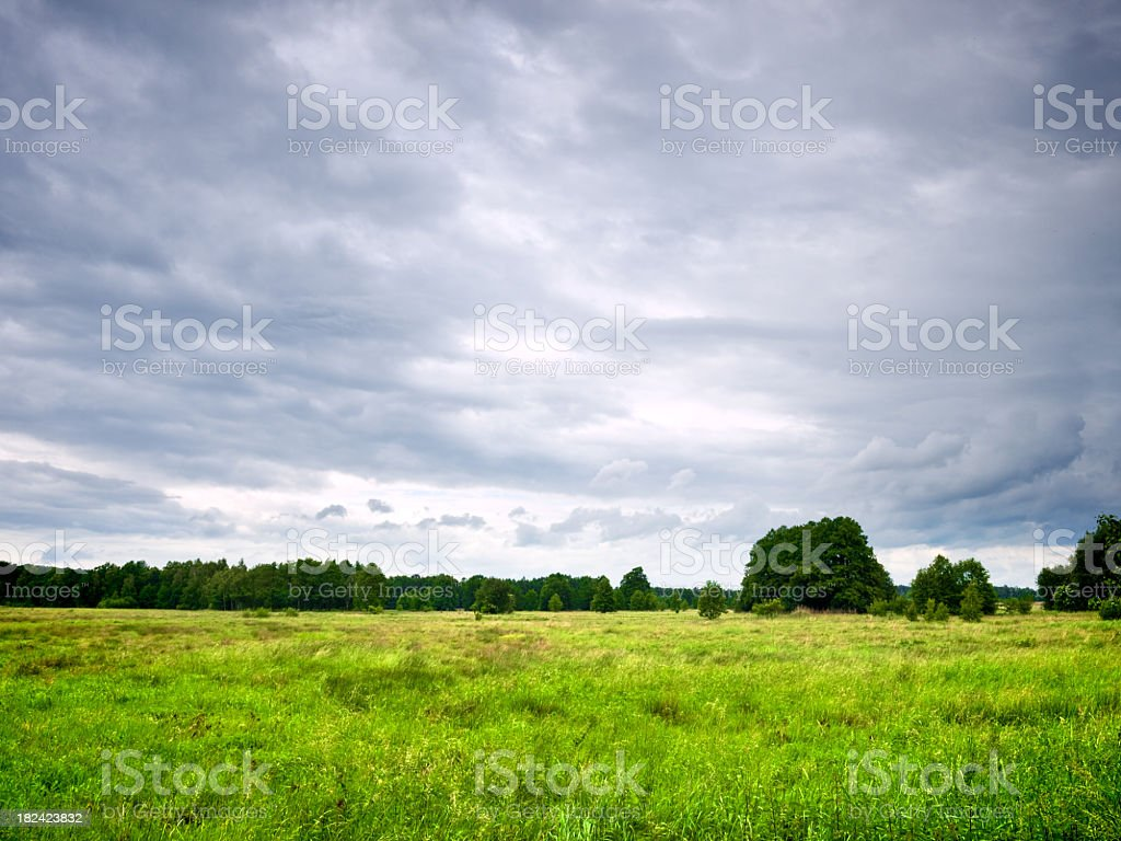 Cloudy almost stormy day sky over field royalty-free stock photo