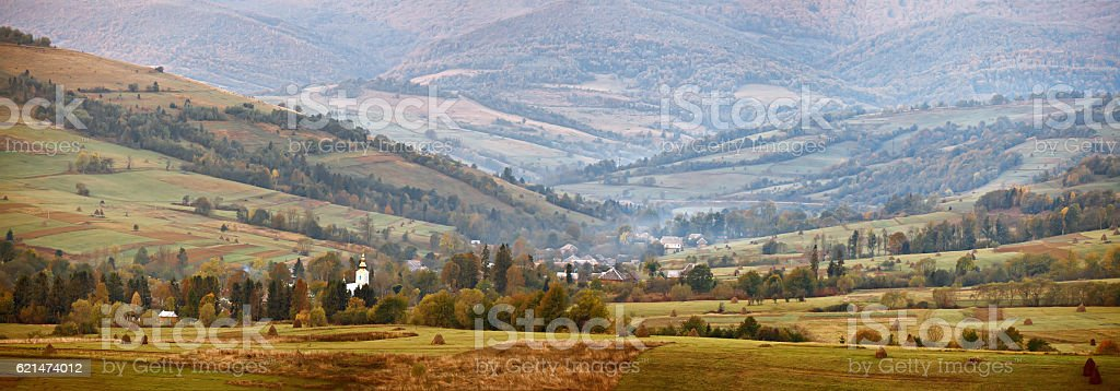 Cloudy autumn panorama in mountain hills. Village in the valley stock photo