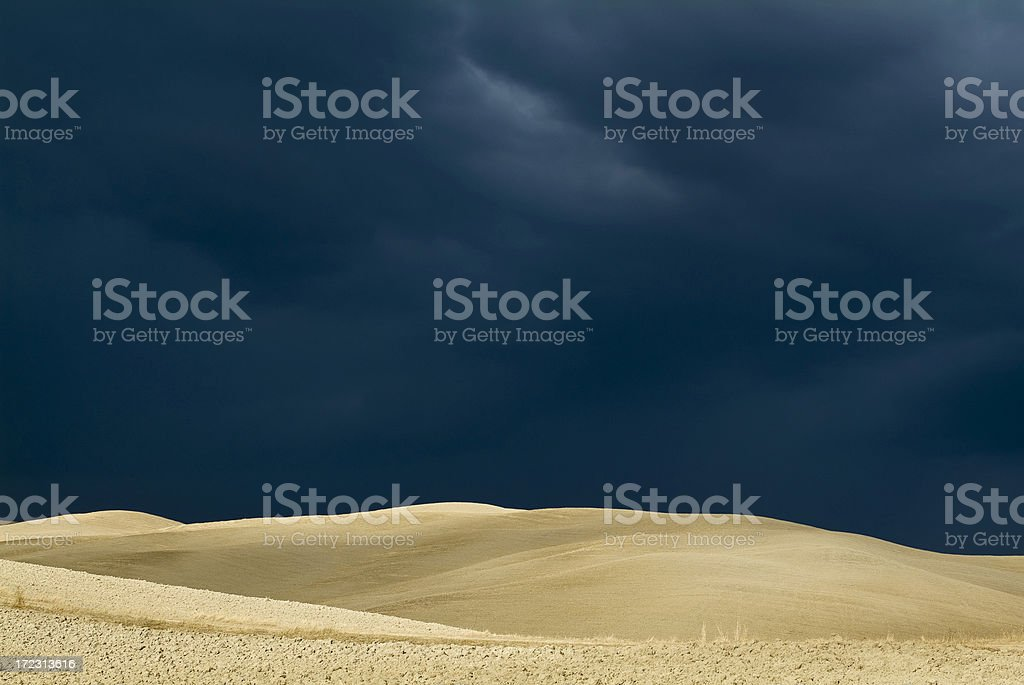Cloudy dark blue sky over beige hills royalty-free stock photo