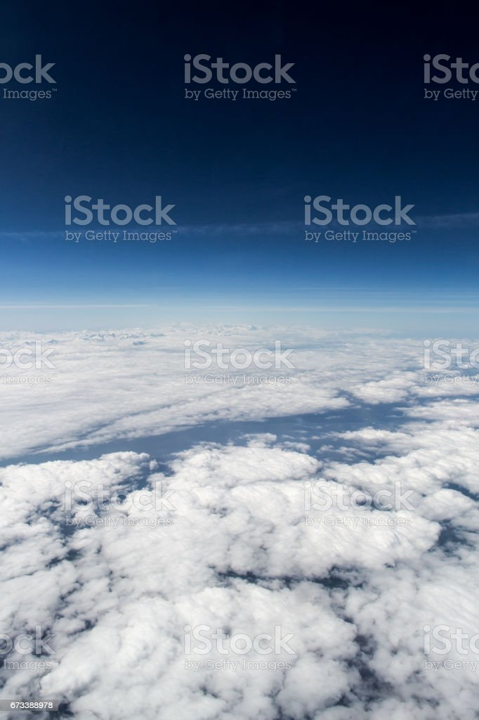 Cloudy skies over europe pictured from high altitude with deep blue skies. stock photo