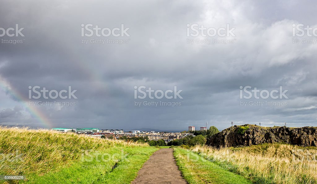 cloudy sky and rainbow above the city stock photo