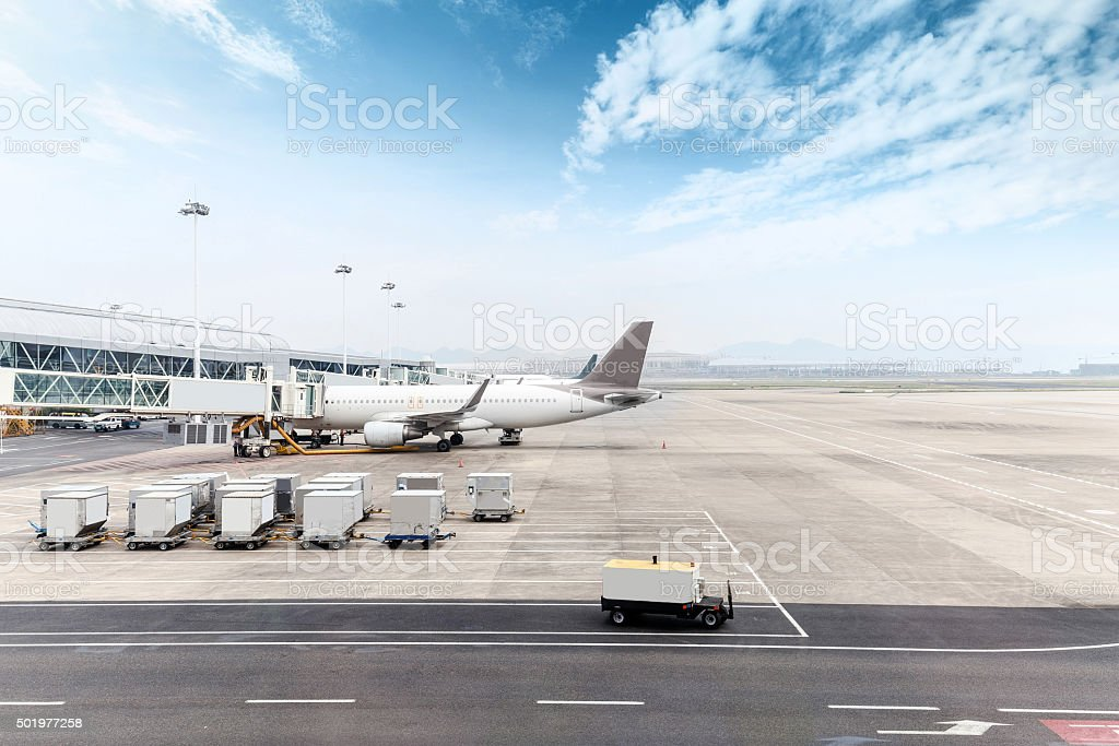 cloudy skyline and airplane on airport ramp stock photo