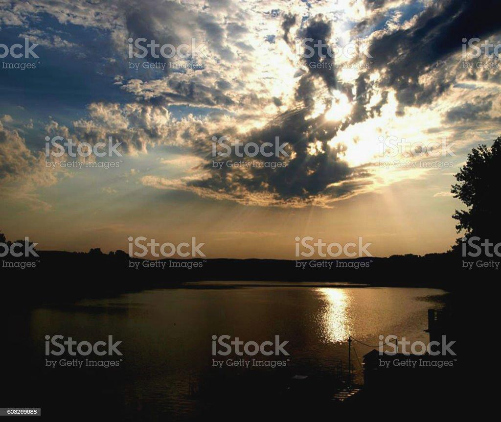 Cloudy sun over the lake stock photo