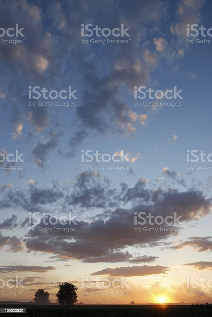 cloudy sunset over countryside field royalty-free stock photo