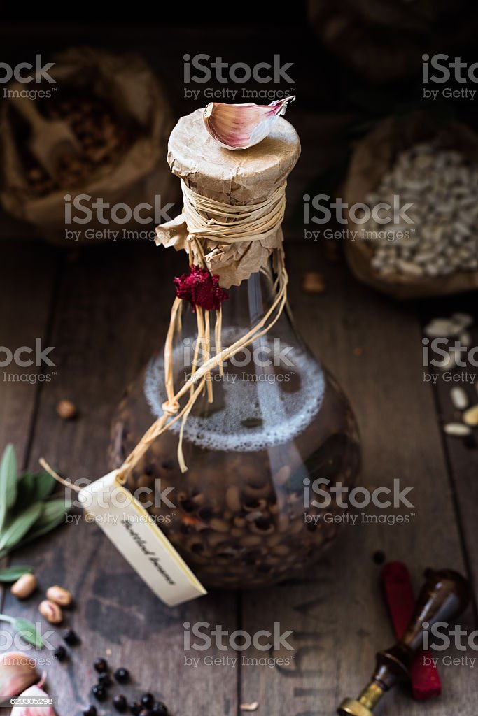 clove of garlic placed over a bottle containing cow pea stock photo