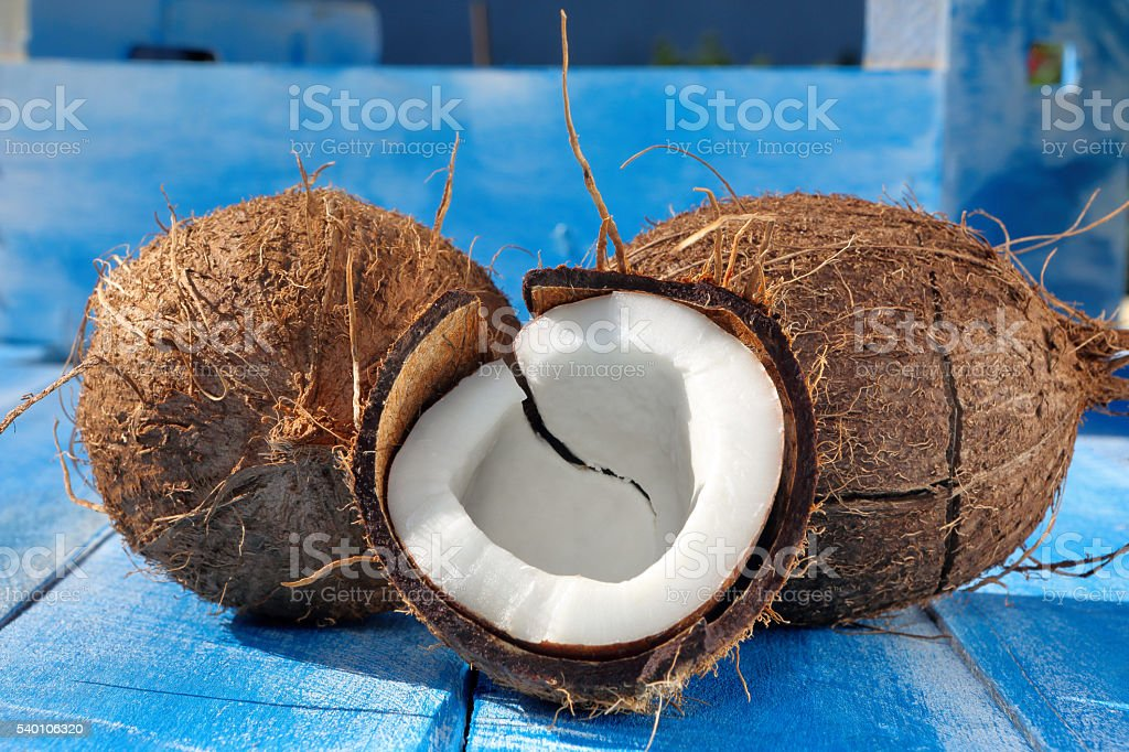 Cloven coconut on a blue wooden background stock photo