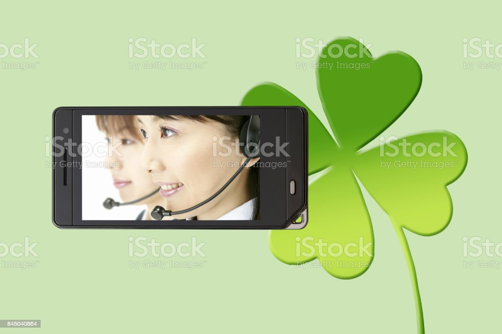 Clover of the operator on the mobile screen and cheesecake stock photo