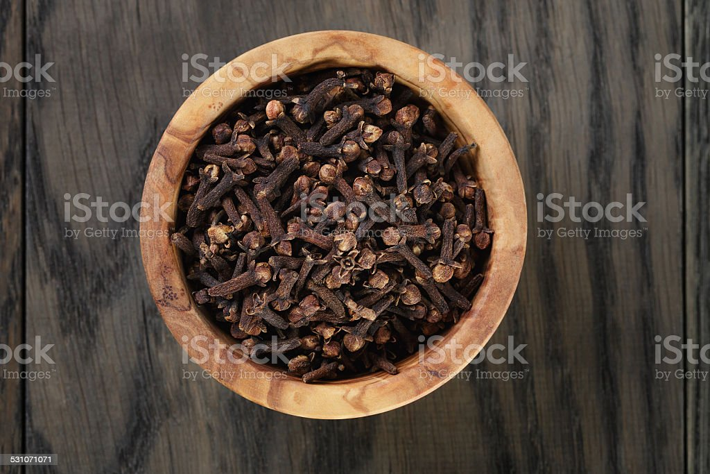 cloves in olive bowl on oak table stock photo