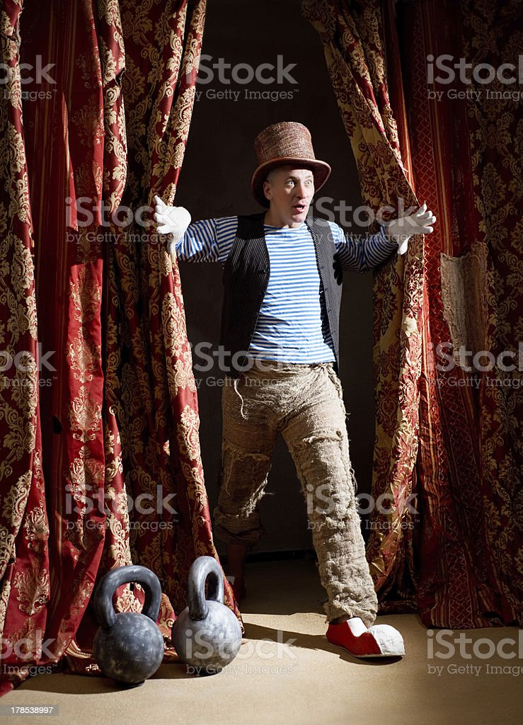 Clown coming out from behind the curtain with surprised face stock photo