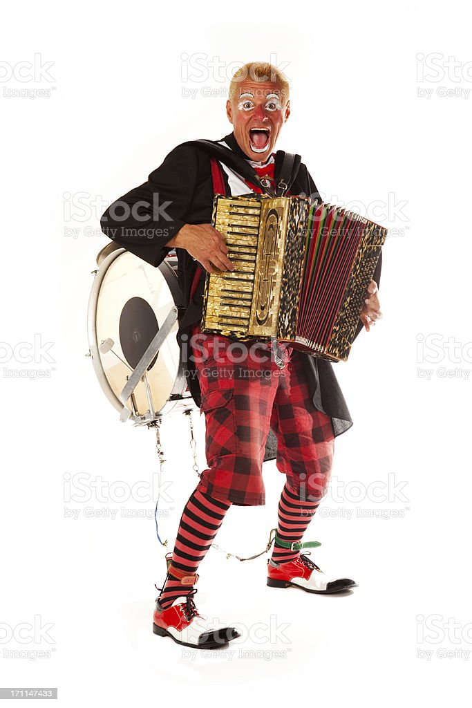 Clown doing tricks with accordion and drum on his back royalty-free stock photo
