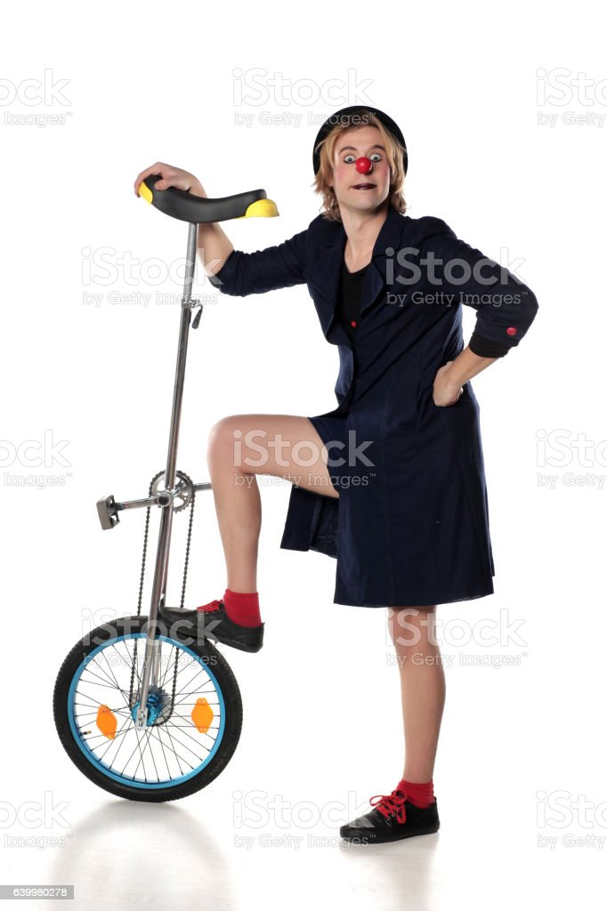 clown entertainer poses with a unicycle stock photo
