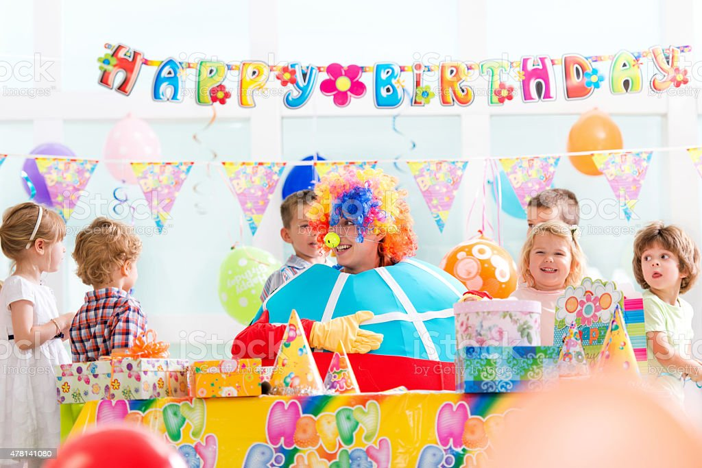 Clown entertaining children on at child's birthday party. stock photo