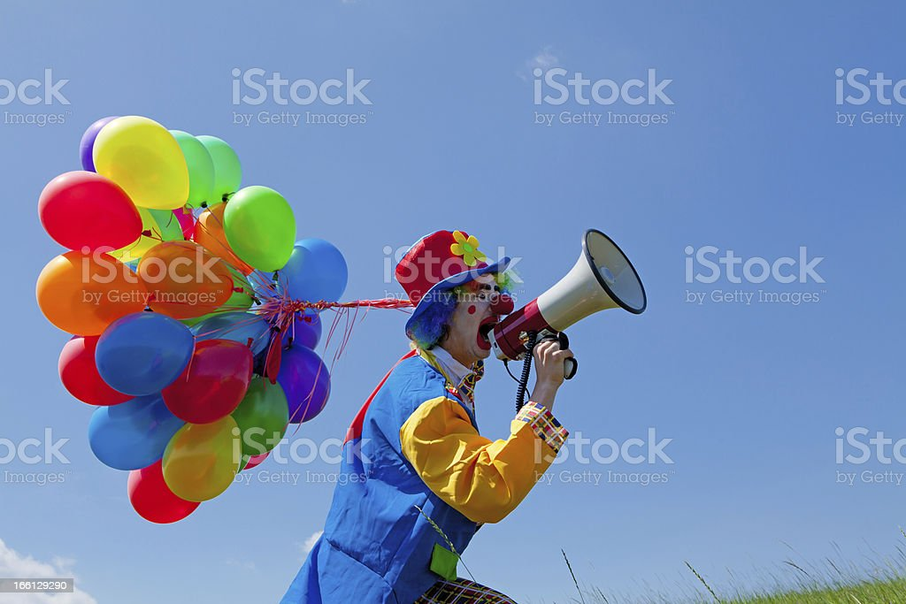 Clown holding balloons and crying  to megaphone royalty-free stock photo