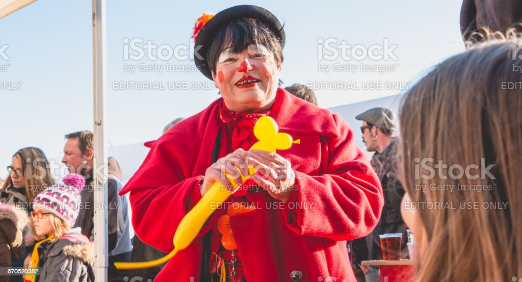 clown makes characters with balls to offer them to the children stock photo
