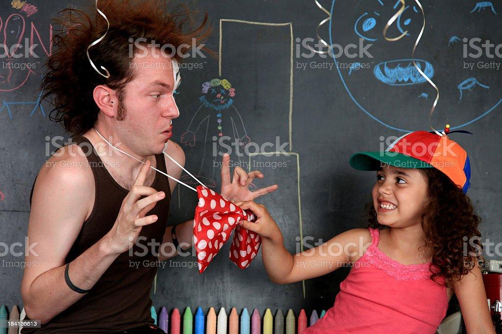 Clown School: child pulling man's bowtie stock photo
