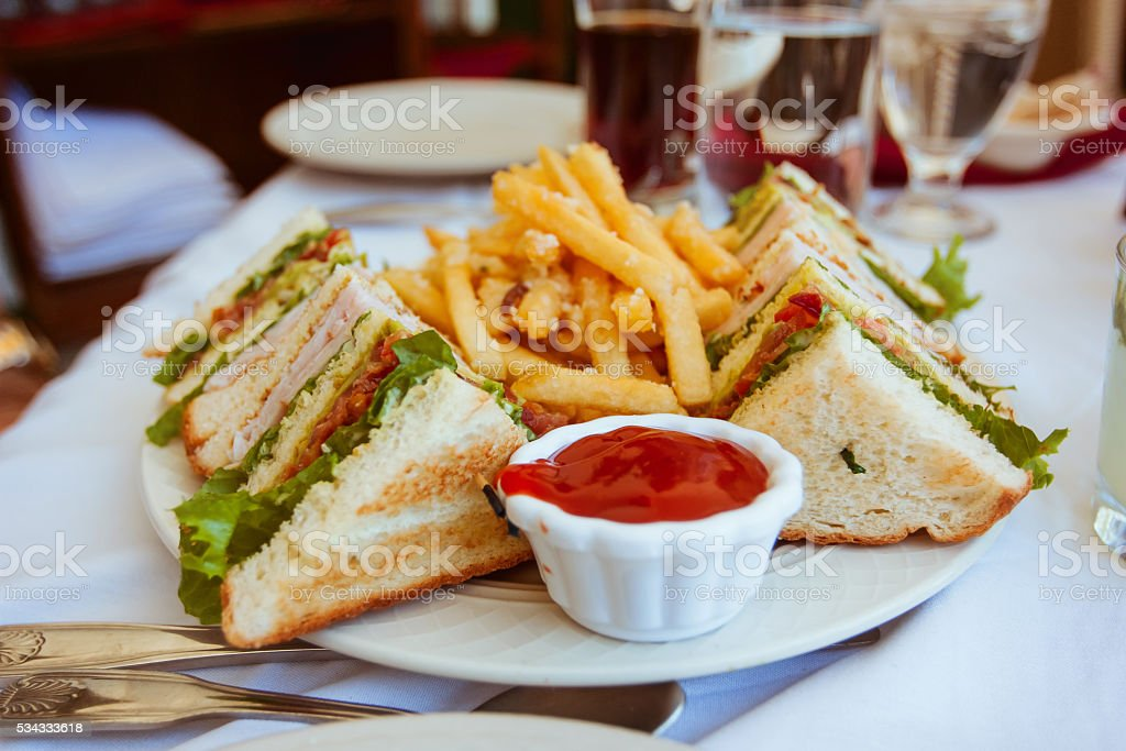 Club sandwiches with french fries on side stock photo