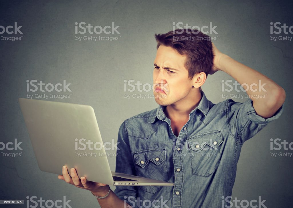 clueless guy having troubles with laptop. Complicated technology stock photo