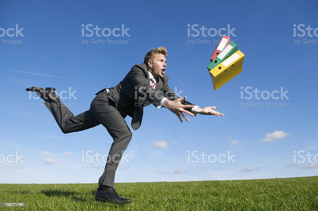 Clumsy Businessman Tripping Outdoors Dropping Handful of Binders stock photo