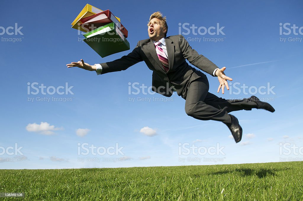 Clumsy Businessman Tripping with File Folders in Meadow stock photo