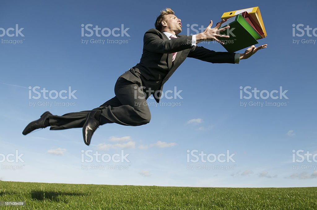 Clumsy Businessman Trips Above Meadow with File Folders royalty-free stock photo